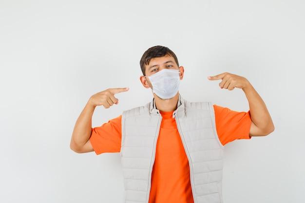 Junger mann, der auf seine medizinische maske in t-shirt, jacke zeigt und selbstbewusst aussieht. vorderansicht.