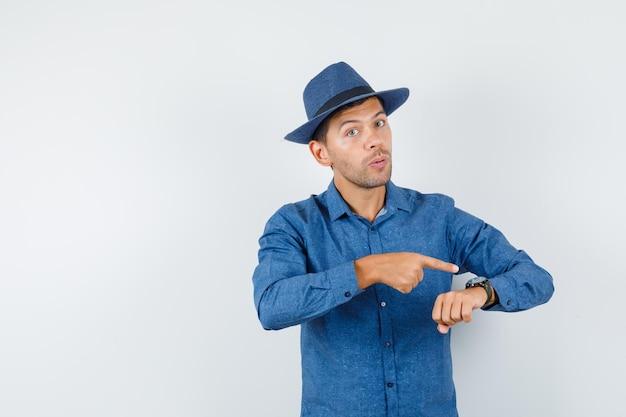 Junger mann, der auf seine uhr am handgelenk in blauem hemd, hut zeigt und vorsichtig schaut. vorderansicht.