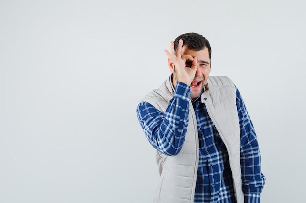 Junger mann, der auf seinem auge im hemd, in der ärmellosen jacke rund macht und amüsiert aussieht. vorderansicht. platz für text