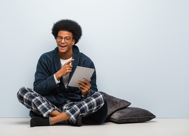 Junger mann, der auf seinem haus sitzt und seine tablette zeigt auf die seite mit dem finger hält