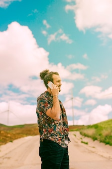 Junger mann, der auf smartphone auf natur in verbindung steht