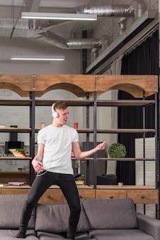 Junger mann, der auf sofa mit kopfhörer auf seinem haupt zu hause tanzt steht