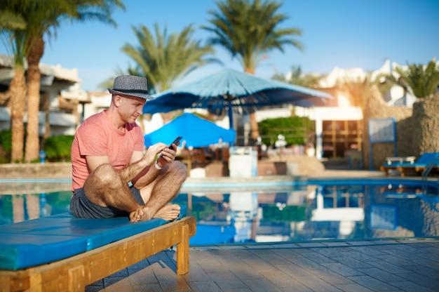 Junger mann, der auf sonnenruhesesseln durch swimmingpool stillsteht und sms am telefon schreibt