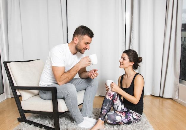 Junger mann, der auf stuhl mit ihrer freundin zu hause trinkt den kaffee sitzt