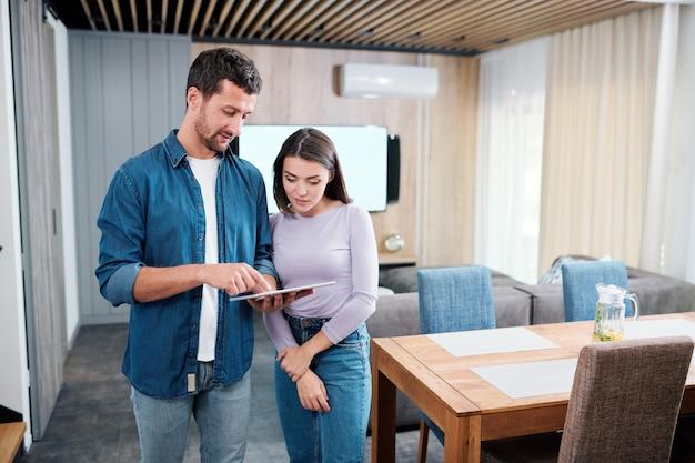 Junger mann, der auf tablettanzeige zeigt, während er seiner frau erklärt, wie man neue intelligente fernbedienungsanwendung verwendet
