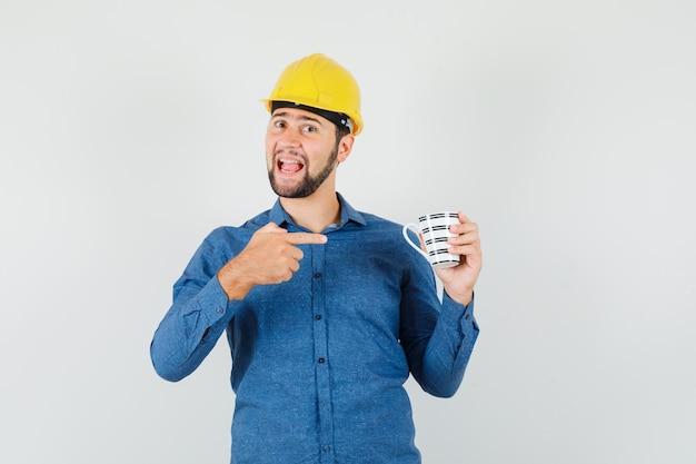 Junger mann, der auf tasse kaffee im hemd, im helm zeigt und glücklich schaut
