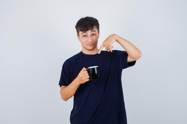 Junger mann, der auf tasse tee im schwarzen t-shirt zeigt und verwirrt schaut. vorderansicht.