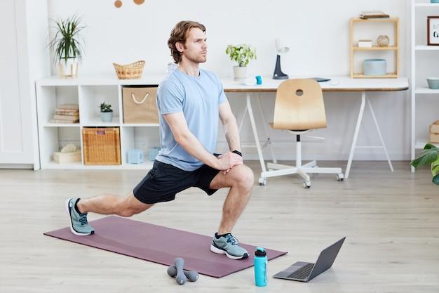 Junger mann, der auf übungsmatte trainiert, die er online-sporttraining auf laptop zu hause beobachtet