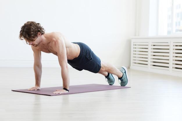 Junger mann, der auf übungsmatte trainiert, die liegestütze während des sporttrainings im fitnessstudio macht