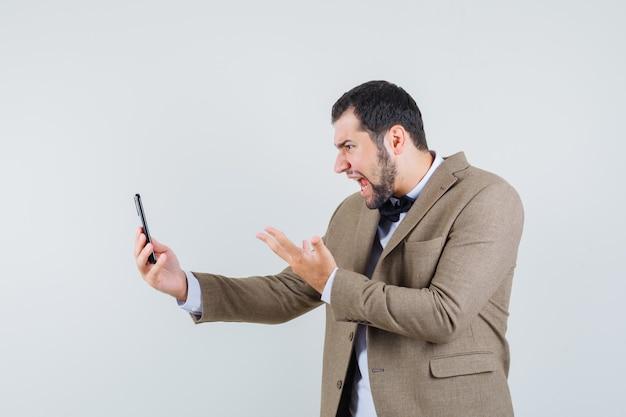 Junger mann, der auf video-chat im anzug schreit und wütend aussieht. vorderansicht.
