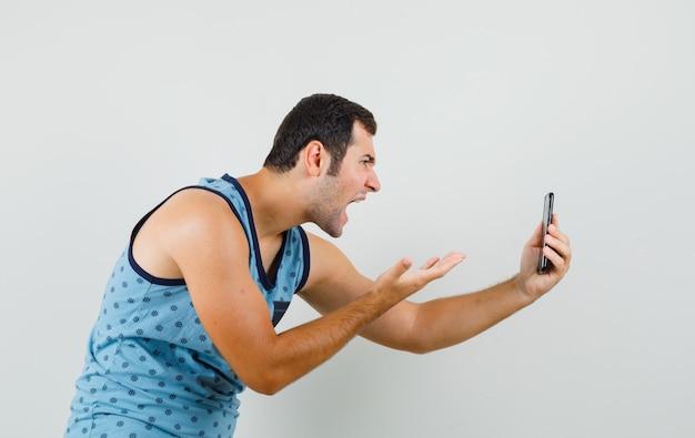 Junger mann, der auf video-chat im blauen unterhemd spricht und nervös schaut.