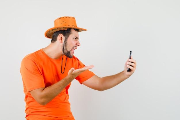 Junger mann, der auf video-chat im orangefarbenen t-shirt, hut spricht und wütend schaut, vorderansicht.