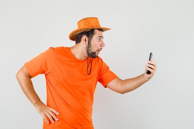 Junger mann, der auf video-chat in orange t-shirt, hut spricht und schockiert schaut, vorderansicht.