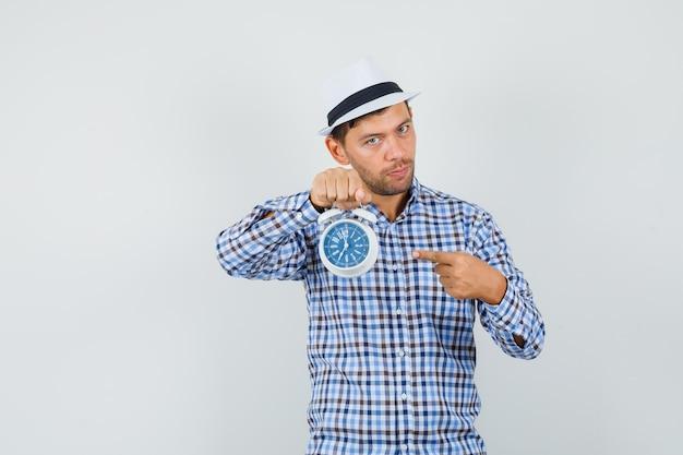 Junger mann, der auf wecker im karierten hemd zeigt