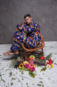 Junger mann, der auf weidenstuhl mit bunten blumenblumensträußen auf weißer kleidung sitzt