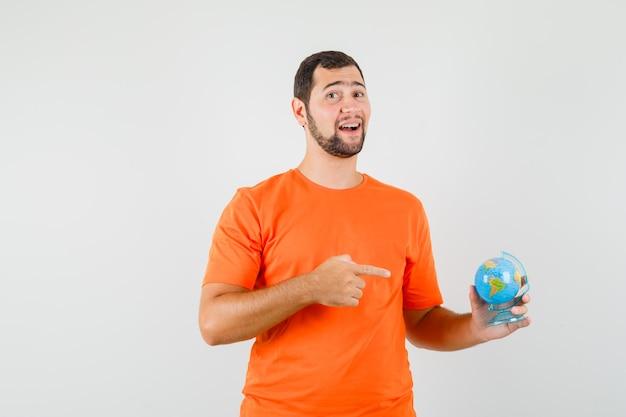 Junger mann, der auf weltkugel im orangefarbenen t-shirt zeigt und freudige vorderansicht schaut.
