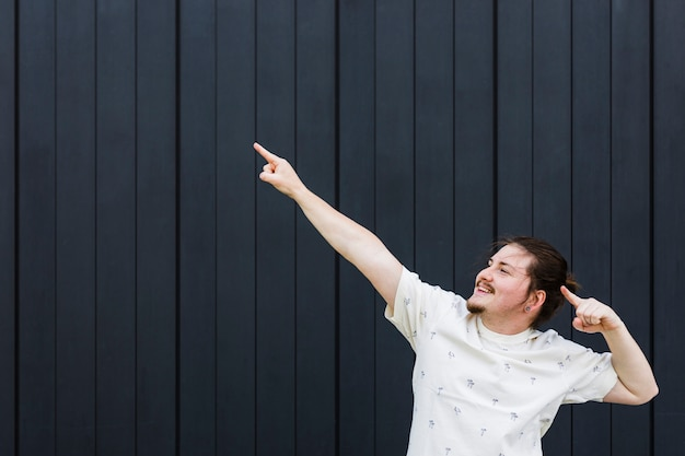 Junger mann, der aufwärts seinen finger gegen schwarze wand zeigt