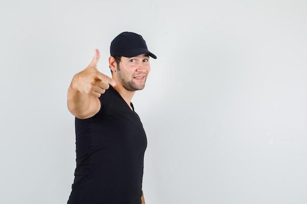 Junger mann, der aufwirft, während er waffengeste im schwarzen t-shirt zeigt