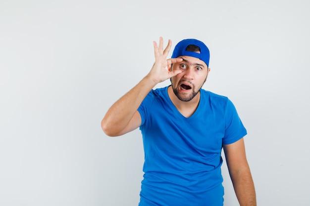 Junger mann, der auge mit den fingern im blauen t-shirt und in der kappe öffnet und seltsam aussieht