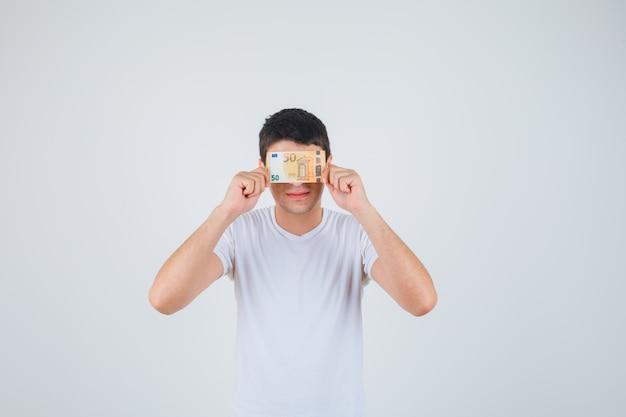 Junger mann, der auge mit euro-banknote im t-shirt bedeckt und fröhlich schaut. vorderansicht.