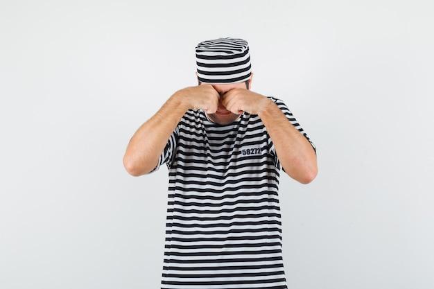 Junger mann, der augen reibt, während er in t-shirt, hut weint und beleidigt aussieht. vorderansicht.