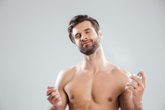 Junger mann, der augen schließt, während er parfüm benutzt