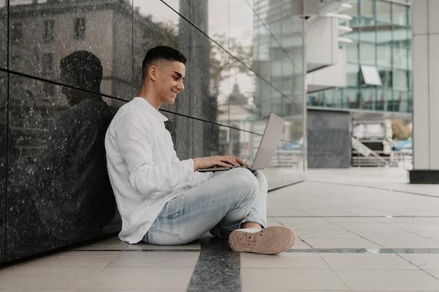 Junger mann, der aus der ferne von einem park aus arbeitet. freiberufler, der draußen arbeitet.