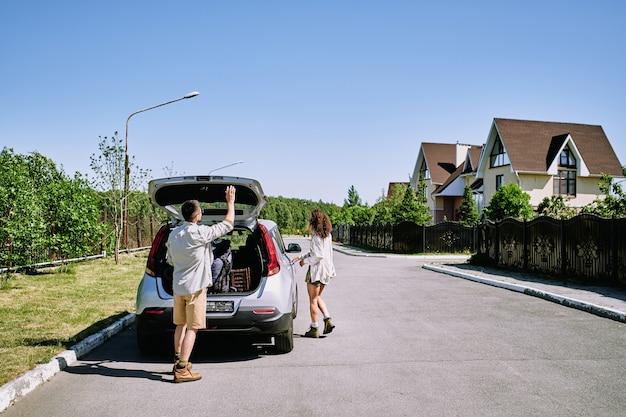 Junger mann, der autokofferraum mit rucksäcken und taschen schließt, während seine frau tür ihres fahrzeugs öffnet, das auf straße in der landschaft steht