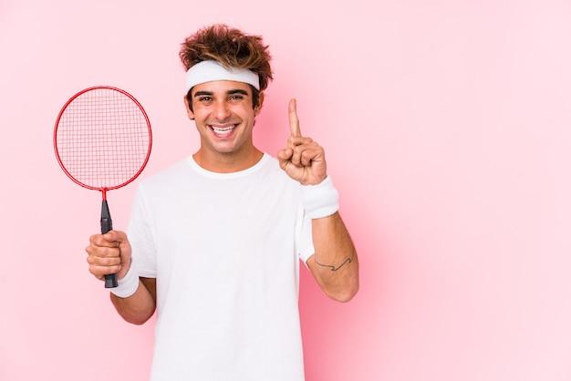 Junger mann, der badminton spielt, isoliert zeigt nummer eins mit finger.