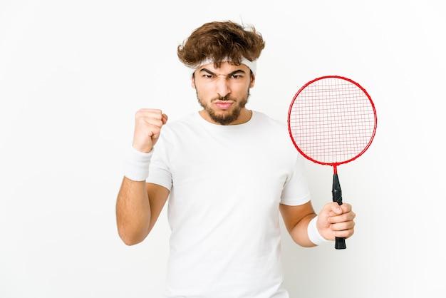 Junger mann, der badminton spielt, zeigt faust nach vorne, aggressiver gesichtsausdruck