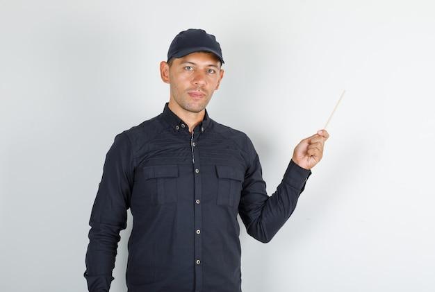 Junger mann, der bambusstäbchen im schwarzen hemd und in der kappe hält