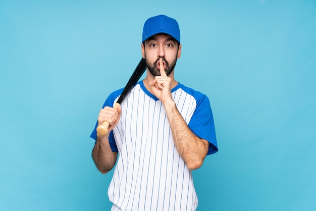 Junger mann, der baseball über dem lokalisierten blau zeigt ein zeichen der ruhegeste einsetzt finger in mund spielt
