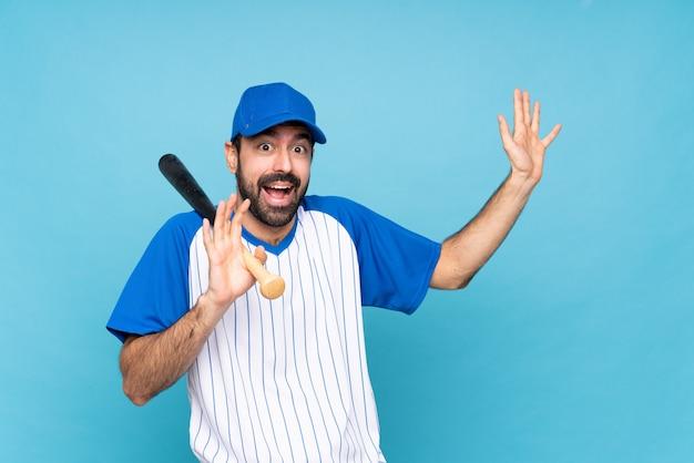 Junger mann, der baseball über der lokalisierten blauen wand nervös und erschrocken spielt