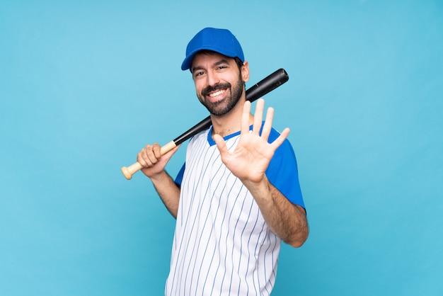 Junger mann, der baseball über der lokalisierten blauen wand zählt fünf mit den fingern spielt