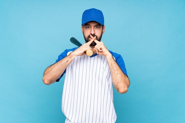 Junger mann, der baseball über der lokalisierten blauen wand zeigt ein zeichen der ruhegeste spielt