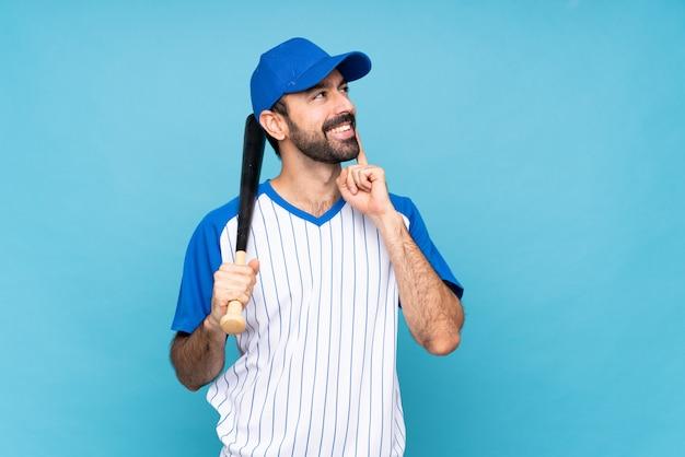 Junger mann, der baseball über lokalisiertem blau denkt eine idee beim oben schauen spielt