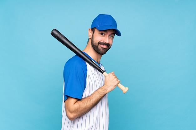 Junger mann, der baseball über lokalisiertem blau mit den armen gekreuzt spielt und vorwärts schaut