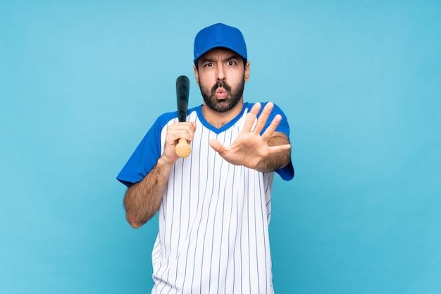 Junger mann, der baseball über lokalisiertem blauem hintergrund nervös spielt, hände zur front ausdehnend
