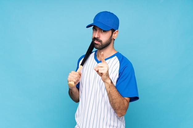 Junger mann, der baseball über lokalisierter blauer wand frustriert spielt und auf die front zeigt