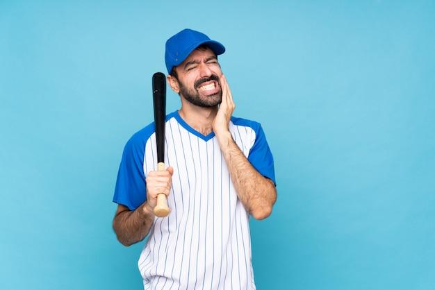 Junger mann, der baseball über lokalisierter blauer wand mit zahnschmerzen spielt