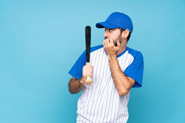 Junger mann, der baseball über lokalisierter blauer wand nervös und erschrocken spielt, hände zum mund setzend