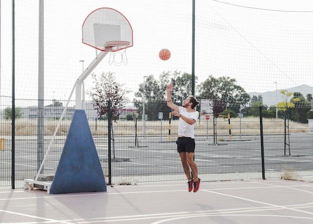 Junger mann, der basketball im band springt und wirft