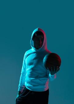 Junger mann, der basketball mit kühlen lichtern spielt