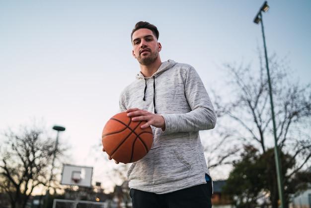 Junger mann, der basketball spielt.