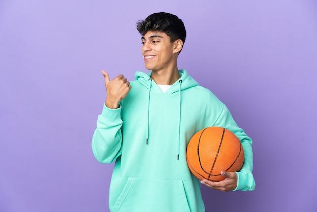 Junger mann, der basketball über isolierte lila wand spielt, die zur seite zeigt, um ein produkt zu präsentieren
