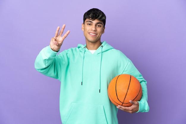 Junger mann, der basketball über lokalisiertem lila hintergrund glücklich spielt und drei mit den fingern zählt