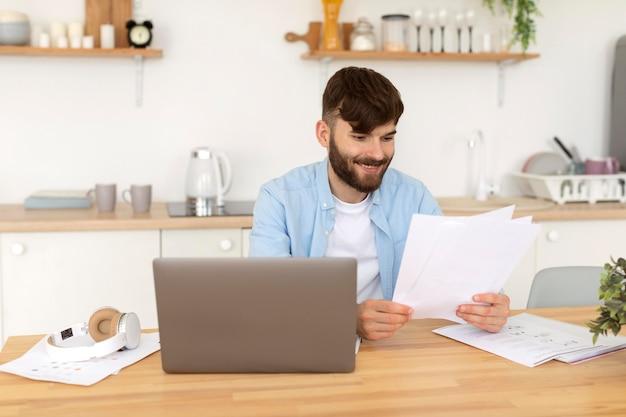 Junger mann, der bei der arbeit an seinem laptop arbeitet