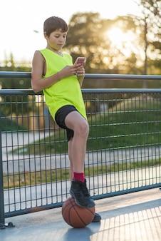 Junger mann, der bei sonnenuntergang ein telefon im freien benutzt