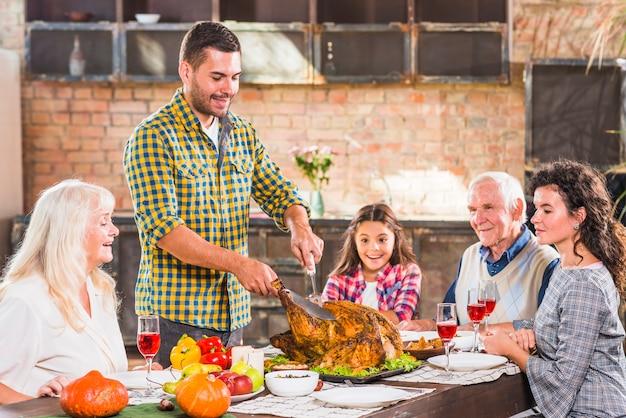 Junger mann, der bei tisch gebackenes huhn mit familie schneidet