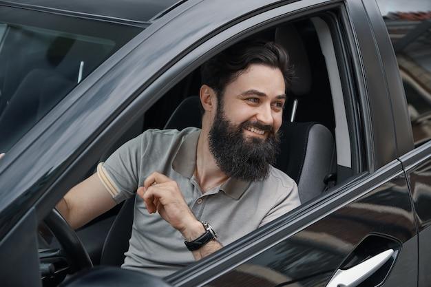 Junger mann, der beim autofahren lächelt